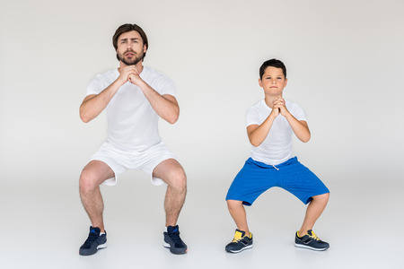 Foto de boy and father squatting together on grey background - Imagen libre de derechos