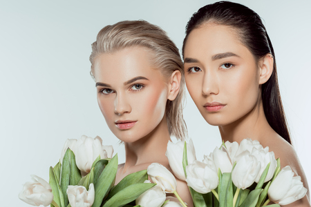 Photo for multicultural girls posing with white tulip flowers, isolated on grey - Royalty Free Image