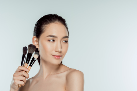 Photo pour attractive asian woman holding makeup brushes, isolated on grey - image libre de droit