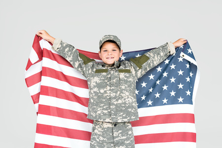 Foto de portrait of cheerful kid in military uniform with american flag isolated on grey - Imagen libre de derechos