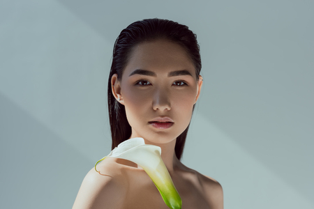 Photo pour beautiful nude asian girl with calla flower, isolated on grey - image libre de droit