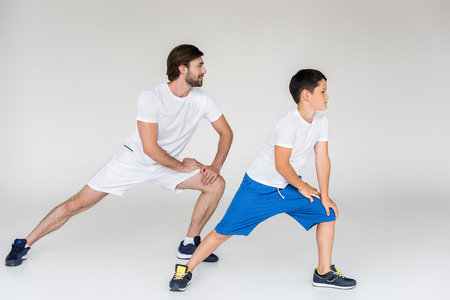 Foto de father and son in white shirts stretching on grey backdrop - Imagen libre de derechos