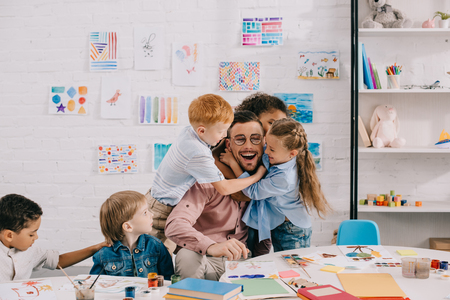 Foto de interracial kids hugging happy teacher at table in classroom - Imagen libre de derechos