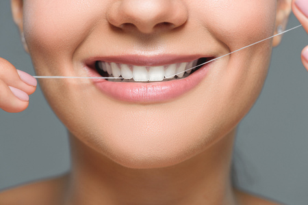 Photo for partial view of smiling woman with beautiful white teeth and dental floss isolated on grey - Royalty Free Image