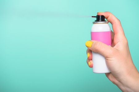 Photo for cropped shot of woman holding spray paint for hair isolated on turquoise - Royalty Free Image
