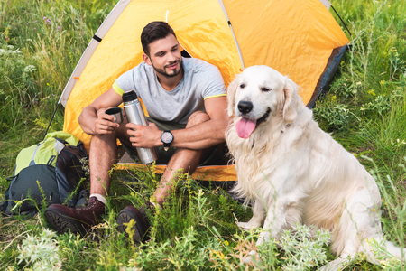 Photo for traveler with thermos sitting in tent and looking at dog - Royalty Free Image