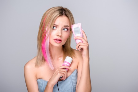 Foto de bewildered young woman with colored bob cut holding hair care supplies isolated on grey - Imagen libre de derechos