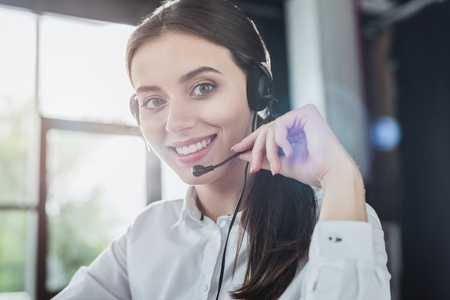 Photo pour beautiful female call center worker with headphones looking at camera - image libre de droit