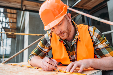 Photo pour handsome builder using measuring tape and pencil at construction site - image libre de droit
