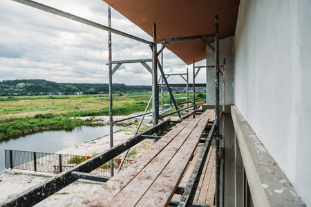 Photo pour scaffolding of construction site of modern building near river - image libre de droit