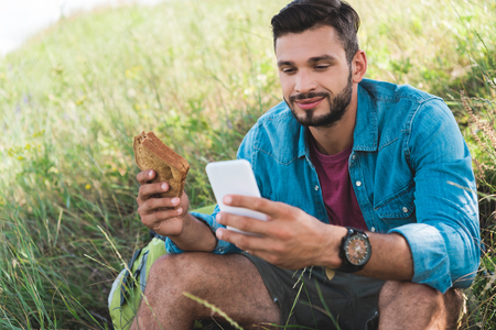 Photo for traveler using smartphone and eating sandwich on summer meadow - Royalty Free Image