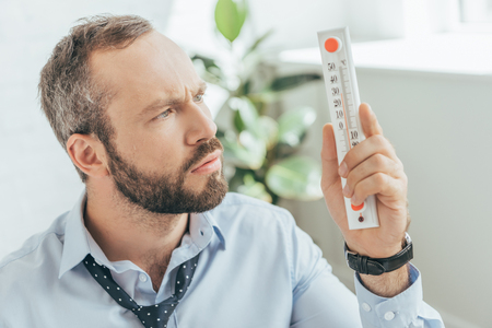 Photo pour confused businessman in hot office looking at thermometer - image libre de droit