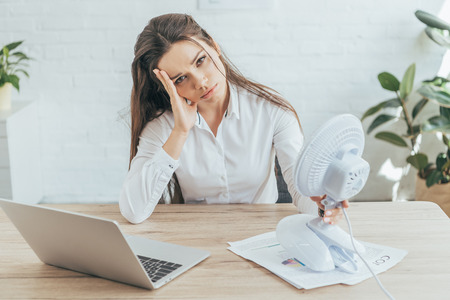 Photo for upset businesswoman sitting at workplace with paperwork, laptop and electric fan - Royalty Free Image