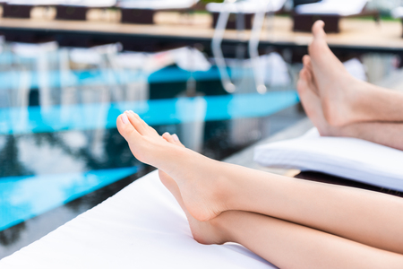 Foto per cropped view of couple relaxing on sunbeds near swimming pool - Immagine Royalty Free