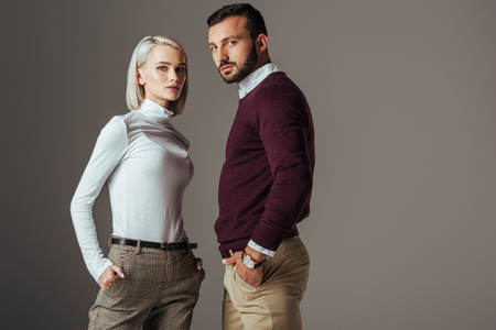 Photo pour couple posing in fashionable autumn outfit, isolated on grey - image libre de droit