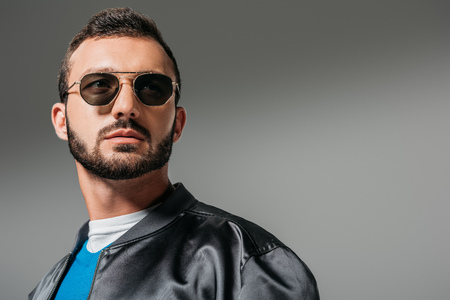 Photo pour bearded man posing in black bomber and sunglasses,  isolated on grey - image libre de droit