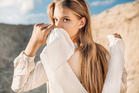 Photo pour beautiful blonde girl with white scarf walking on sand dune - image libre de droit