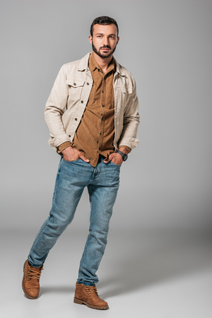 Photo pour handsome man posing in corduroy shirt and autumn jacket with hands in pockets of jeans, on grey - image libre de droit