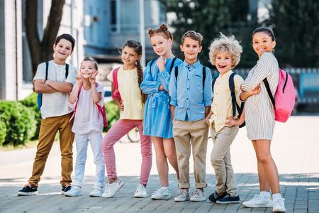 Foto de group of adorable pupils posing in school garden - Imagen libre de derechos