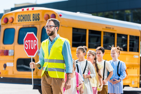 Photo pour traffic guard crossing road with schoolchildren in front of school bus - image libre de droit