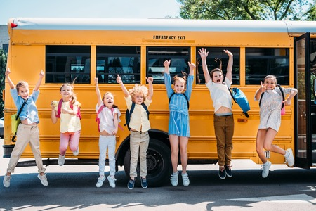Photo pour group of happy pupils jumping in front of school bus and looking at camera - image libre de droit