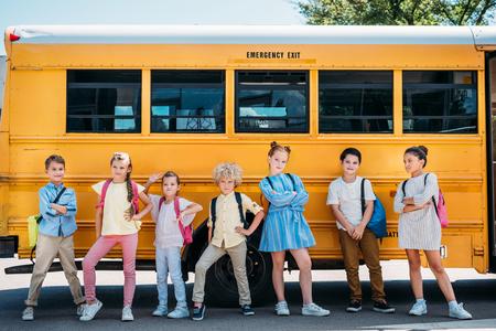 Photo pour group of adorable schoolchildren posing in front of school bus - image libre de droit