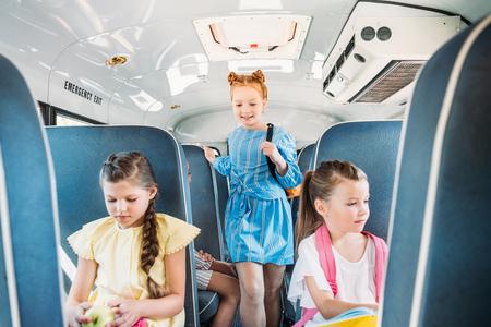 Foto de adorable little pupils riding on school bus during excursion - Imagen libre de derechos