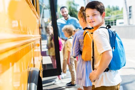 Photo pour little schoolboy entering school bus with classmates while teacher standing near door - image libre de droit