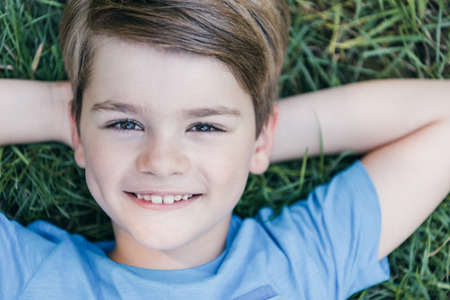 Photo for top view of happy child lying on grass and smiling at camera - Royalty Free Image