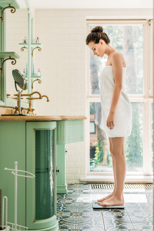 Photo pour side view of beautiful young woman in towel standing on digital scales in bathroom - image libre de droit