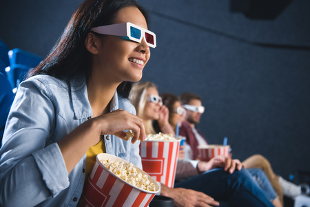 Photo pour smiling asian woman in 3d glasses with popcorn watching movie in cinema - image libre de droit