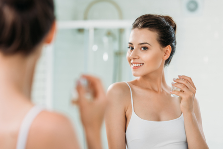 Photo pour beautiful young woman holding perfume bottle and looking at mirror in bathroom - image libre de droit