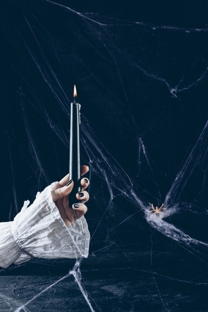 Photo pour partial view of creepy woman holding black candle in darkness with spider web - image libre de droit