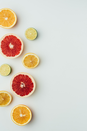 Photo for top view of grapefruit, lemon, lime and orange slices, on grey with copy space - Royalty Free Image