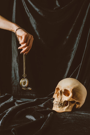 Photo pour cropped view of woman holding vintage clock on the chain near skull on black cloth - image libre de droit