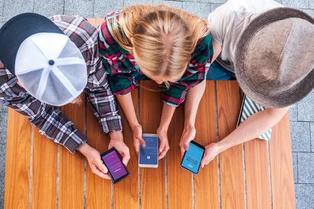 Foto de overhead view of young friends using smartphones with social media apps - Imagen libre de derechos