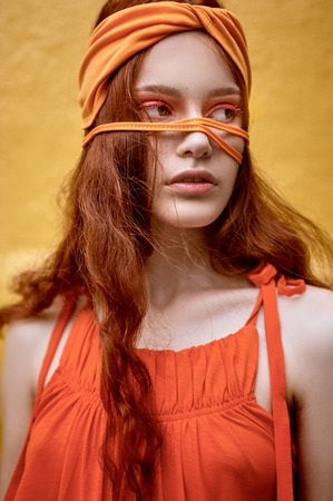 Photo pour beautiful redhead woman with makeup posing in orange headband - image libre de droit
