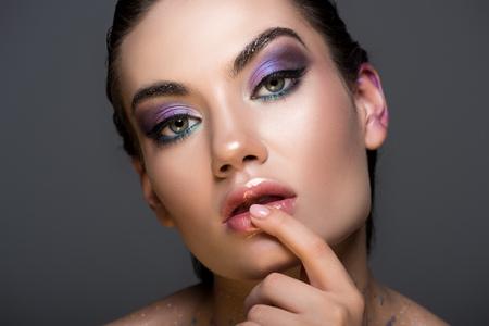 Foto de sensual thoughtful woman with glitter makeup, isolated on grey - Imagen libre de derechos