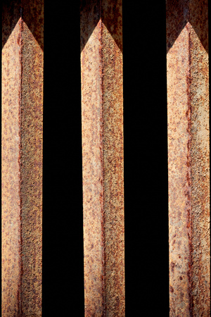 Photo for close up view of rust fence with black background behind - Royalty Free Image