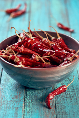 Foto de close up view of spicy chili peppers in bowl on blue wooden surface - Imagen libre de derechos
