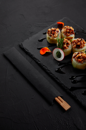 Photo pour close-up view of delicious sushi roll with creamy eel and kimchi mayonnaise on slate board and chopsticks - image libre de droit