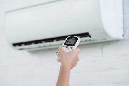 Foto de cropped shot of woman pointing at air conditioner hanging on brick wall with remote control - Imagen libre de derechos