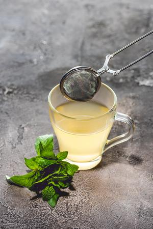 Photo pour healthy tea with mint and tea strainer on grey surface - image libre de droit