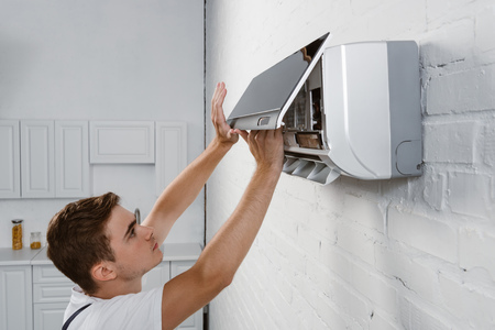 Photo pour repairman taking off dirty filter from air conditioner hanging on white brick wall - image libre de droit