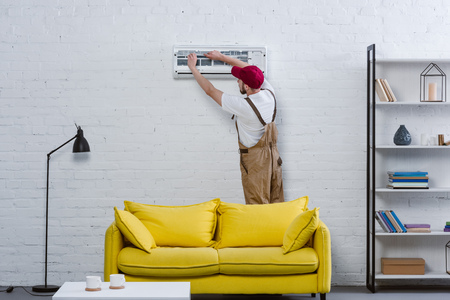 Photo pour professional repairman changing filter for air conditioner hanging on white brick wall - image libre de droit