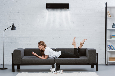 Foto de happy young woman using smartphone on couch under air conditioner hanging on wall - Imagen libre de derechos