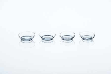 Photo for close up view of contact lenses arranged on white backdrop - Royalty Free Image