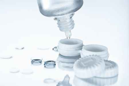 Photo for close up view of contact lenses and its storage equipment on white backdrop - Royalty Free Image