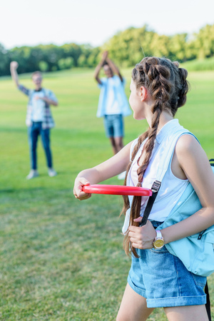 Photo for beautiful teenage girl throwing flying disc to friends in park - Royalty Free Image
