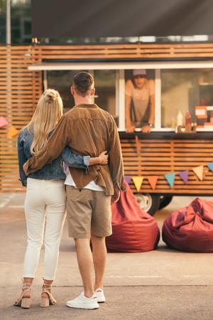 Foto de back view of couple standing near food truck - Imagen libre de derechos